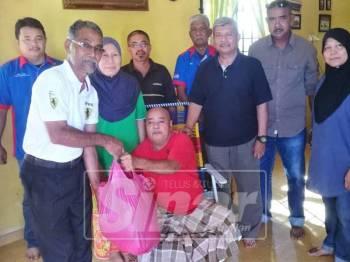 Azizan (tiga, kanan) bersama rombongan ahli GRVATM menyerahkan sumbangan kepada Abdul Halim (duduk, tengah) selepas mengadakan siri kunjungan ziarah warga veteran ATM kurang upaya di Parlimen Parit Buntar hari ini.