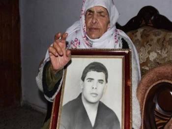 Ibu Fares Baroud memegang potret lelaki terbabit di rumahnya di kem pelarian Al-Shanti