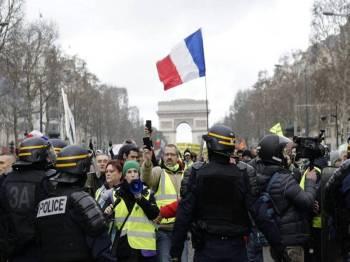 Penunjuk perasaan ves kuning berhimpun berhampiran Champs-Elysees hari ini untuk terus menekan Presiden Emmanuel Macron. - Foto AP