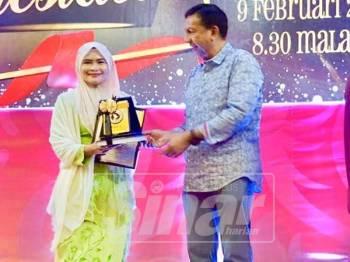 Zulkifli menyampaikan anugerah khas kepada wakil Sinar Harian, Nor Khalilah Gusti Hassan (kiri) pada majlis itu malam tadi.