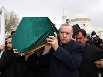 Presiden Erdogan membawa keranda salah seorang daripada sembilan beranak yang maut dalam runtuhan bangunan itu.