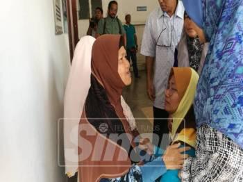 Nurdiana Alwani (kanan) meminta maaf kepada ibu arwah, Masitah di perkarangan Bilik Forensik HSNZ, pagi tadi.