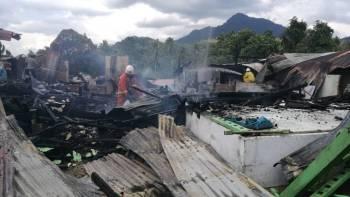 Anggota bomba bertungkus lumus memadam kebakaran dua rumah dan tiga premis di Jalan Hospital, Jeli, hari ini.