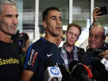 Hakeem al-Araibi (tengah) ditemani bekas kapten pasukan kebangsaan Australia Craig Foster (kiri) ketika tiba di Lapangan Terbang Melbourne hari ini. - Foto AFP