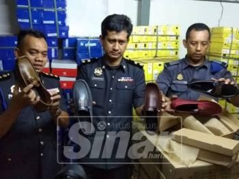 Ahmad Ahrazzuddin (tengah) bersama pegawai penguat kuasa KPDNHEP menunjukkan sebahagian kasut tiruan yang dirampas.