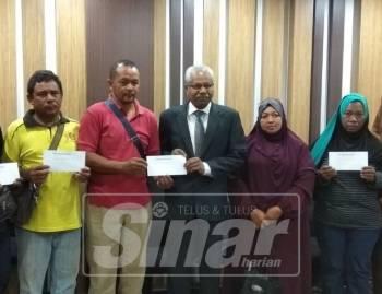 Sivanesan (tengah) menyerahkan sumbangan kepada waris mangsa kebakaran rumah kedai di Jelapang di Bangunan Perak Darul Ridzuan.