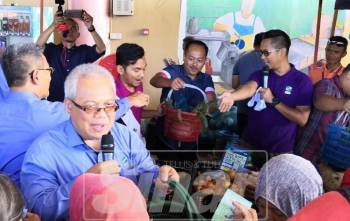 Ishak (tengah pegang mikrofon) ketika membantu jualan murah di Bazar Peduli Rakyat RTC Tunjung hari ini.