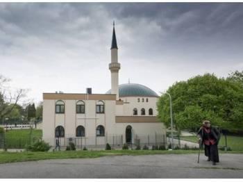 Seorang wanita berjalan di hadapan Pusat Islam Vienna.