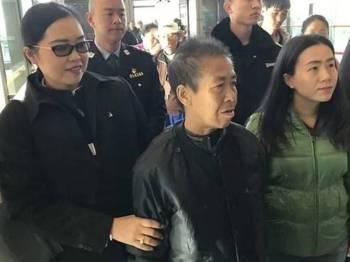 Kaeomanee (tengah) diiringi anaknya (dua kanan) dan anggota imigresen ketika mahu menaiki pesawat pulang ke Thailand.