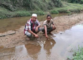 Abdullah (kiri) bersama penduduk kampung menunjukkan ikan yang mati akibat pencemaran sungai di Baroh Pial.