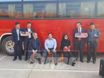 Othsman (duduk ditengah) bersama dengan Fatimah (duduk sebelah kiri) dan Wan Junidi (duduk sebelah kanan) serta Mustapha (berdiri sebelah kanan) sambil memegang bendera Malaysia menghantar rombongan rakyat Malaysia pulang di Lapangan Terbang Antarabangsa Siem Reap.