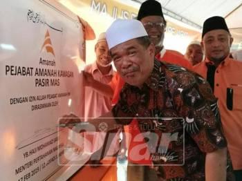 Mohamad menurunkan tandatangan sempena perasmian Pejabat Amanah kawasan Pasir Mas di Kampung Jias.