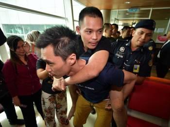 Seorang tahanan, Mark Roger,24, didukung oleh seorang rakannya selepas mengalami kecederaan pada kaki di Lapangan Terbang Antarabangsa Kuching hari ini. - Foto Bernama
