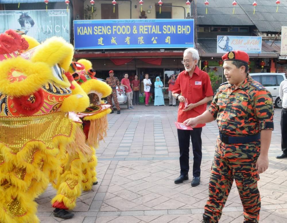 Azlimin (kanan) dan Raja Bahrin sewaktu meraikan komuniti Kampung Cina pada Kempen Keselamatan Kebakaran sempena Tahun Baharu Cina 2019.