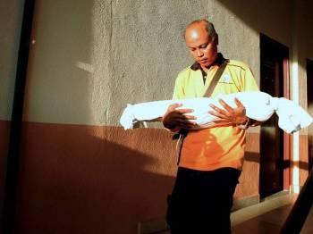 Supian Samsuri, 42, memangku jenazah anaknya, Nur Qhaisara Medina, 2, di Unit Forensik Hospital Raja Permaisuri Bainun, hari ini. - Foto Bernama