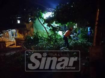 Pembersihan pokok di kawasan gerai dan rumah mangsa oleh anggota APM