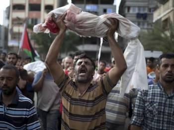 Seorang lelaki Palestin mengangkat jenazah anaknya yang terbunuh dalam serangan Israel di wilayah yang diduduki.