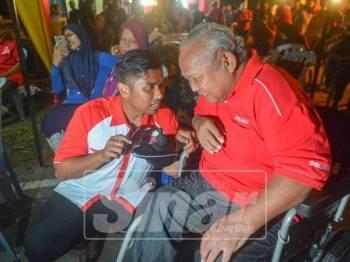 Muhammad Aiman beramah mesra dengan Mohd Muslim Salamat, 67, di Kampung Rinching Hilir, sebentar tadi.