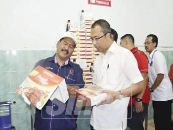 Ahmad Jais (kiri) menunjukkan produknya kepada Pegawai Daerah Kluang, Ismail Abu (kiri).