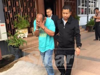Tertuduh (tengah) dikawal anggota SPRM keluar dari mahkamah selepas didakwa.