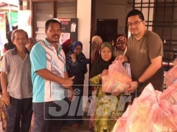 Tuan Peng (kanan) menyampaikan sumbangan berupaya barangan keperluan harian kepada salah seorang penduduk Kampung Melayu Pandan yang terjejas akibat banjir kilat baru-baru ini.