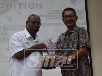 Ramakrishnan (kiri) menerima cenderahati dari Pengarah Politeknik Mersing, Hassan Siraj selepas merasmikan Program Ponggal & Tradition 2019.