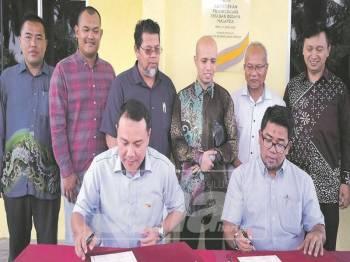 Mohd Kahirul dan Mohd Muktafi menandatangani dokumen berkaitan pada Majlis Penyerahan Pusat Pemerhatian Kelip-kelip Sungai Pakeh.