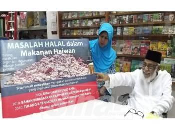 Mohamed menunjukkan papan tanda mengenai masalah halal dalam makanan haiwan dalam sidang media tadi.