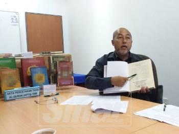 Feisal menunjukkan al-Quran yang dicop dan mendapat kelulusan daripada Lembaga Pengawalan Pelesenan dan Percetakan al-Quran Kementerian Dalam Negeri.
