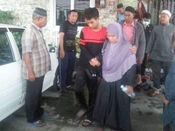 Muhammad Ariff (tengah) ditemani ibunya sewaktu hendak dibawa ke Hospital Parit Buntar bagi mendapatkan rawatan lanjut dengan menaiki ambulans. FOTO: Kredit pembaca