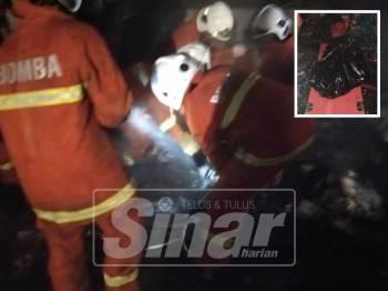 Anggota bomba mengeluarkan mayat mangsa.