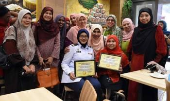 Aida (kiri) dan Ummu Khair masing-masing menerima sijil penghargaan daripada Masdiana (tengah)