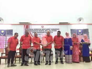 Mahadzir (lima, kanan) menerima buah tangan daripada Ketua UMNO Bahagian Parit, Datuk Mohd Nizar Zakaria (tiga, kiri) pada majlis berkenaan, hari ini.