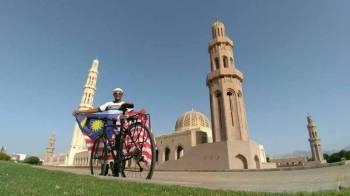 Suliman mengibarkan bendera Malaysia di Masjid Agung Sultan Qaboos, Oman.