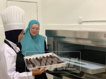 Norul bersama salah seorang pekerjanya menyiapkan tempahan.