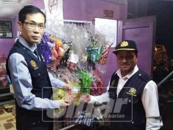 Dr Sin Yew (kiri) dan Mohd Jaafar menunjukkan rokok yang dirampas dalam operasi dijalankan.