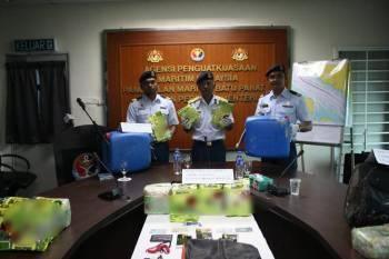 Aminuddin (tengah) menunjukkan dadah yang disorok dalam bungkusan teh cina tersebut.