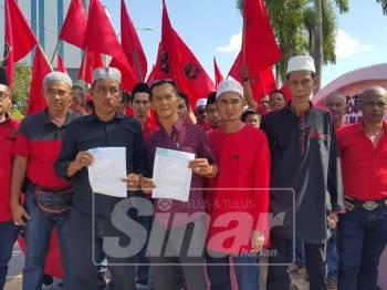 Ahmad Sukri (tengah) menunjukkan salinan laporan polis selepas membuat laporan terhadap individu menghina Islam dan Nabi Muhammad SAW.