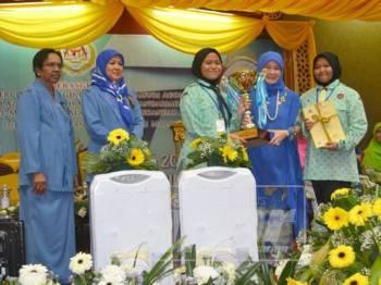 Tunku Hajah Azizah Aminah Maimunah Iskandariah (dua kanan) menyampaikan hadiah kepada pasukan Pahang yang menjuarai pertandingan choral speaking sempena Hari Peringatan Sedunia Peringkat Kebangsaan di IPG Kota Bharu, malam tadi.