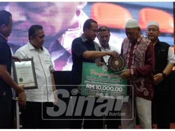 Mohd. Mustafa (dua kanan) mewakili anaknya yang menerima penghargaan Wira Darul Iman sempena Himpunan Belia dan Beliawanis Terengganu 2019 (Hebat 2019) dan Pelancaran Program Kesukarelawan Terengganu (T-VOLT) di Stadium Negeri Terengganu, malam tadi.