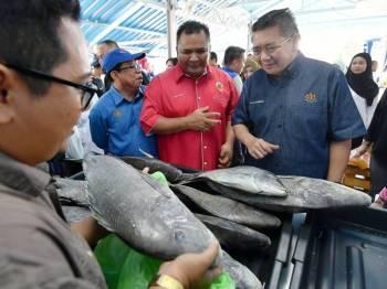 Menteri Pertanian dan Industri Asas Tani, Datuk Salahuddin Ayub (kanan) melawat gerai jualan ikan merah batu semasa melawat gerai jualan sempena Program Kecemerlangan Jabatan Perikanan Malaysia (DOF) di Laman Perikanan, Tapak Ekspo Pertanian Malaysia Serdang (MAEPS) hari ini. - Foto Bernama