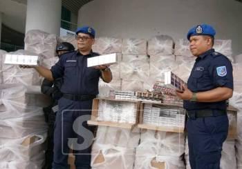 Mohd Khairuddin (kiri) menunjukkan sebahagian rokok yang dirampas.