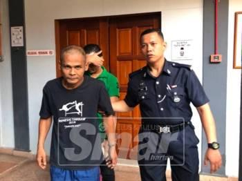 Tertuduh (kiri) dikawal polis keluar dari mahkamah selepas dihukum.