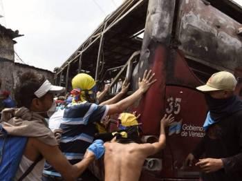 Penunjuk perasaan Venezuela menolak sebuah bas yang dibakar ketika protes di bandar Urena, Tachira, selepas Presiden Maduro umum penutupan sementara sempadan dengan Colombia.- Foto AFP