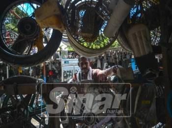 Raju sedang memilih barang dikehendaki pelanggan di kedainya. Foto: SHARIFUDIN ABDUL RAHIM