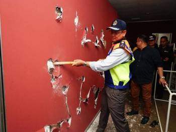 Azman memecahkan dinding premis yang diubah suai untuk dijadikan bilik.