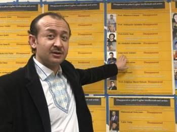 Abudwaris Ablimit menunjukkan gambar abangnya ketika satu pertemuan di Washington bagi meningkatkan kesedaran tentang kehilangan ahli keluarga etnik Uighur di Xinjiang.- Foto AP