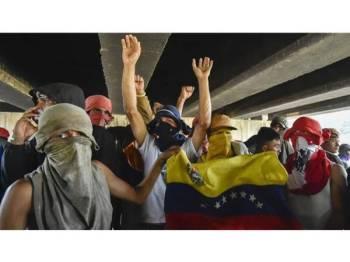 Sekumpulan penunjuk perasaan berlindung di bawah Jambatan Simon Bolivar, Cucuta Colombia bersempadan dengan Venezuela. - Foto AFP