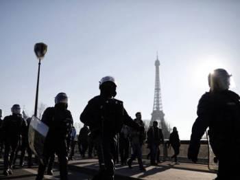 Penunjuk perasaan ves kuning dikawal ketat polis rusuhan ketika berhimpun di Paris, Perancis. - Foto AP