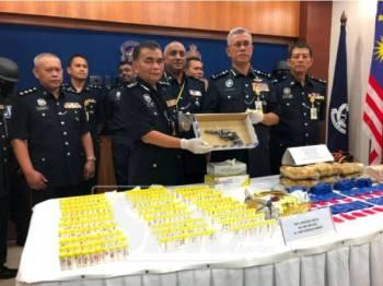Hasanuddin (dua, kanan) bersama Ketua Polis Daerah Kota Bharu, Asisten Komisioner Abdul Rahim Daud menunjukkan pistol yang dirampas daripada suspek.